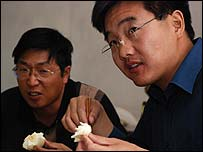 Project leader Sun Guicai (r) eats dinner