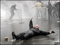 A Georgian opposition supporter falls down as police disperse a rally in Tbilisi on 7 November