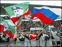 Chechens wave Russian and Chechen flags with the head of Ramzan Kadyrov on them