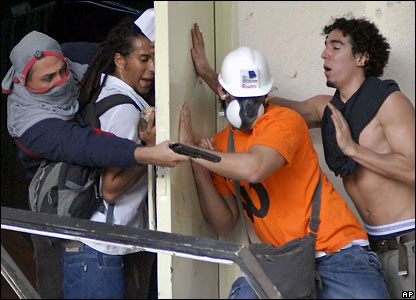 A supporter of President Hugo Chavez points a gun at anti-Chavez students in Caracas, Venezuela on 7 November 2007