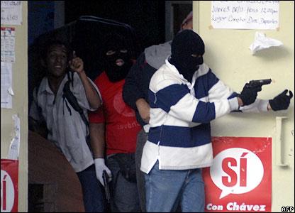 A masked gunman points a gun towards students in Caracas, Venezuela, on 7 November 2007