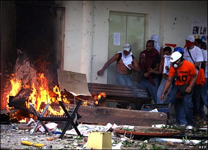 Students take cover next to a barricade set alight in Caracas, Venezuela, on 7 November 2007