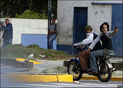 A man on a motorcycle points a handgun at students in Caracas, Venezuela, on 7 November 2007