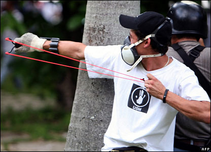 A student aims a slingshot during clashes between students in Caracas, Venezuela, on 7 November 2007