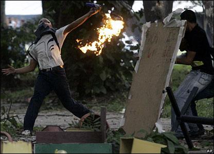 An anti-Chavez demonstrator throws a firebomb in Caracas, Venezuela, on 7 November 2007