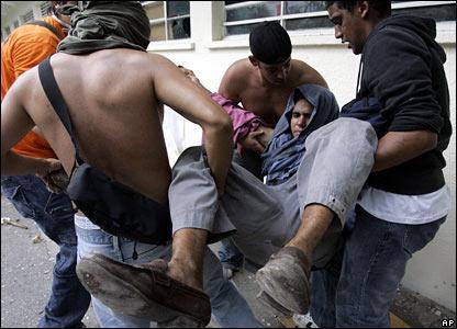 An injured anti-Chavez demonstrator is carried by friends in Caracas, Venezuela, on 7 November 2007