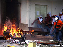 Students take cover next to a barricade set alight in Caracas, Venezuela, on 7 November 2007