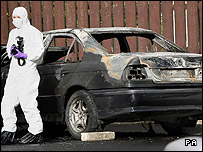 Forensics officer at burned-out car