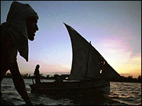 A Kenyan man watches a Dhow sail past