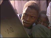 Villagers looking at pictures of the children on a BBC laptop
