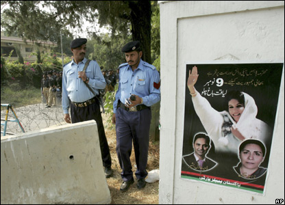 Police guard a street next to a poster of Benazir Bhutto, 9 Nov 07
