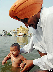 An Indian Sikh and his son at the holy sarover in Amritsar's Golden Temple during the Bandi Chhor Divas festival
