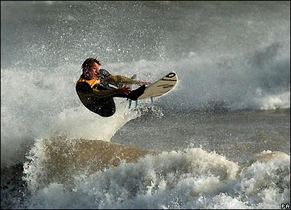 Surfer off east coast of England during a tidal surge