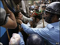 A supporter of Benazir Bhutto is taken away by police in Islamabad (9 November)