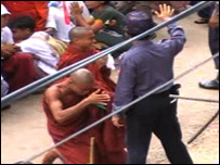 A monk kneels in front of the police during the protests