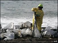 A worker cleans up oil at Muir Beach, California