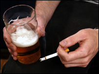 Someone drinking a pint of beer and smoking a cigarette