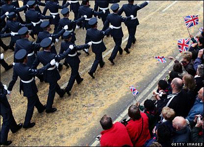 Crowds waving flags at parade