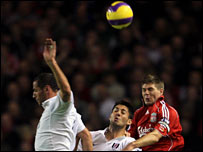Steven Gerrard jumps to head the ball