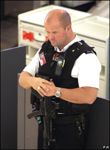 Armed policeman stands observed two minute's silence at Heathrow Airport