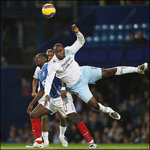 Darius Vassell is challenged by Pompey's Sulley Muntari