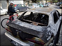 A man looks at a burnt out car in Rome, 12 November 2007