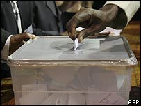 Kenyan voter places a ballot into a box