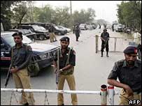Полицейское оцепление на улице в Лахоре, где задержана Бхутто