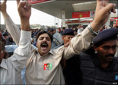 Police arrest supporters of opposition leader Benazir Bhutto outside her residence in Lahore, Pakistan