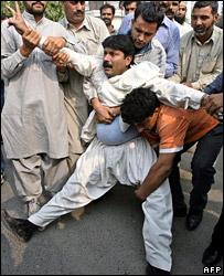 A protester is arrested near the police roadblock outside Benazir Bhutto's home in Karachi
