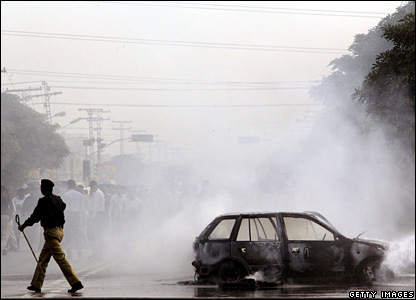 A Pakistani policeman walks past the burnt wreckage of car that was set alight in protest by supporters of Ms Bhutto