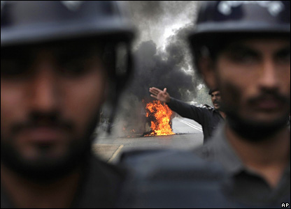 Pakistani police stand in front of a car that was set alight in protest by supporters of Ms Bhutto