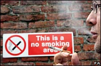 Man smoking next to a no smoking sign