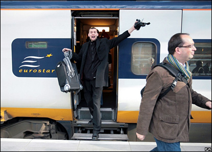 A passenger cheers as he gets of the Eurostar train at St Pancras