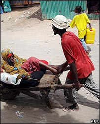 Elderly Somali woman carried in a wheelbarrow