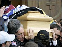 The casket of Gabriele Sandri, covered by football team scarves, is carried by his father Giorgio Sandri (left) and his brother Cristiano (right) in Rome