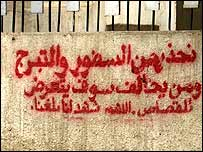 "A warning on a Basra wall against wearing ""immodest dress"""