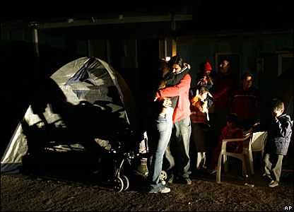 Residents embrace next to a tent in Maria Elena, Chile, Nov. 14, 2007