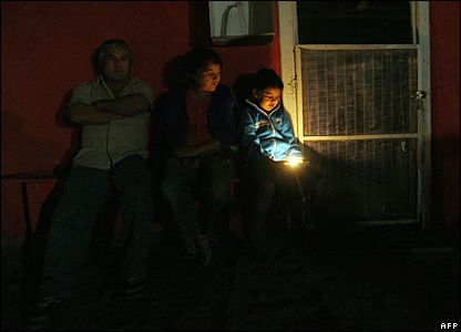A family wait outside their house in the mining town of Maria Elena, Chile, 14 November, 2007