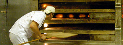 Rafal Sgraja, 25, checks bread in oven