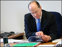 John Swinney reading at his desk
