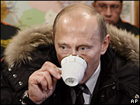 Russian President Vladimir Putin drinks a tea during a meeting with workers in Siberia
