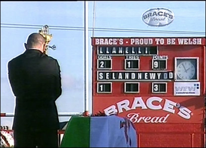 Eisteddfod swordbearer Robin McBryde stands alongside the coffin. The scoreboard records the famous Llanelli victory over the All Blacks in 1972.