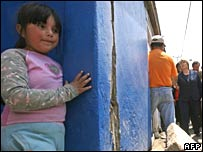 A littl girl hides behind a wall in quake-hit Tocopilla as Chilean President Michelle Bachelet (R) visits on 15 November 2007