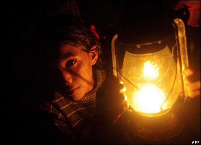 A Bangladeshi girl holds a lamp in a cyclone shelter near Mongla, 15 November 2007