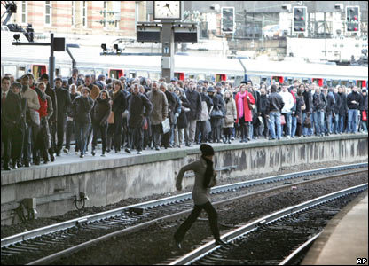 A woman runs on the tracks, as passengers walk on a crowded platform at the Saint Lazare station in Paris, Thursday 15 November