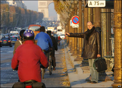 A man hitch-hikes on the Champs Elysees in Paris, 16 November