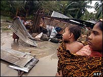 A woman collects corrugated iron sheets from her destroyed house in Mongla
