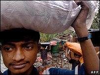 Bangladeshis carry their belongings at their village Kanainagar, in Mongla
