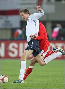 England striker Peter Crouch fends off Austria's Yuksel Sariyar